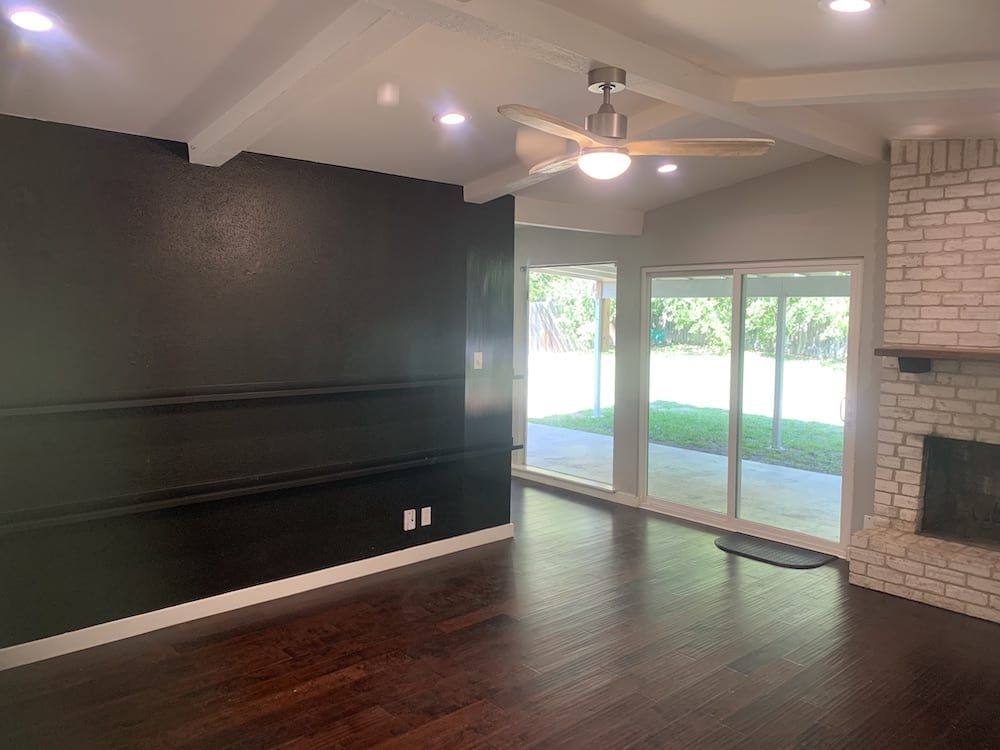 living room with black accent wall and wood floors