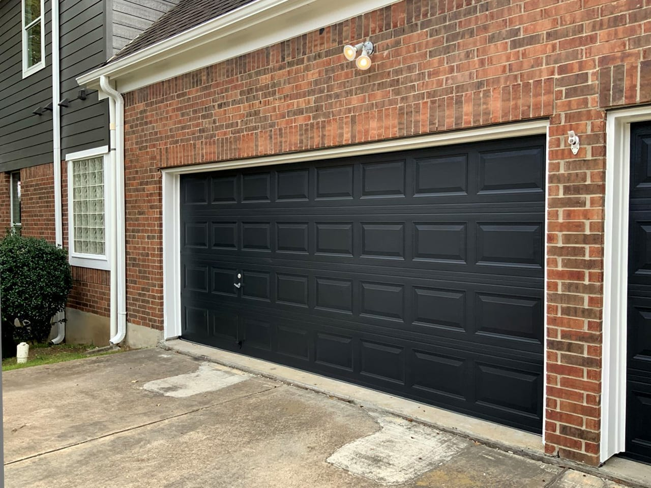 dark painted garage door on brick home