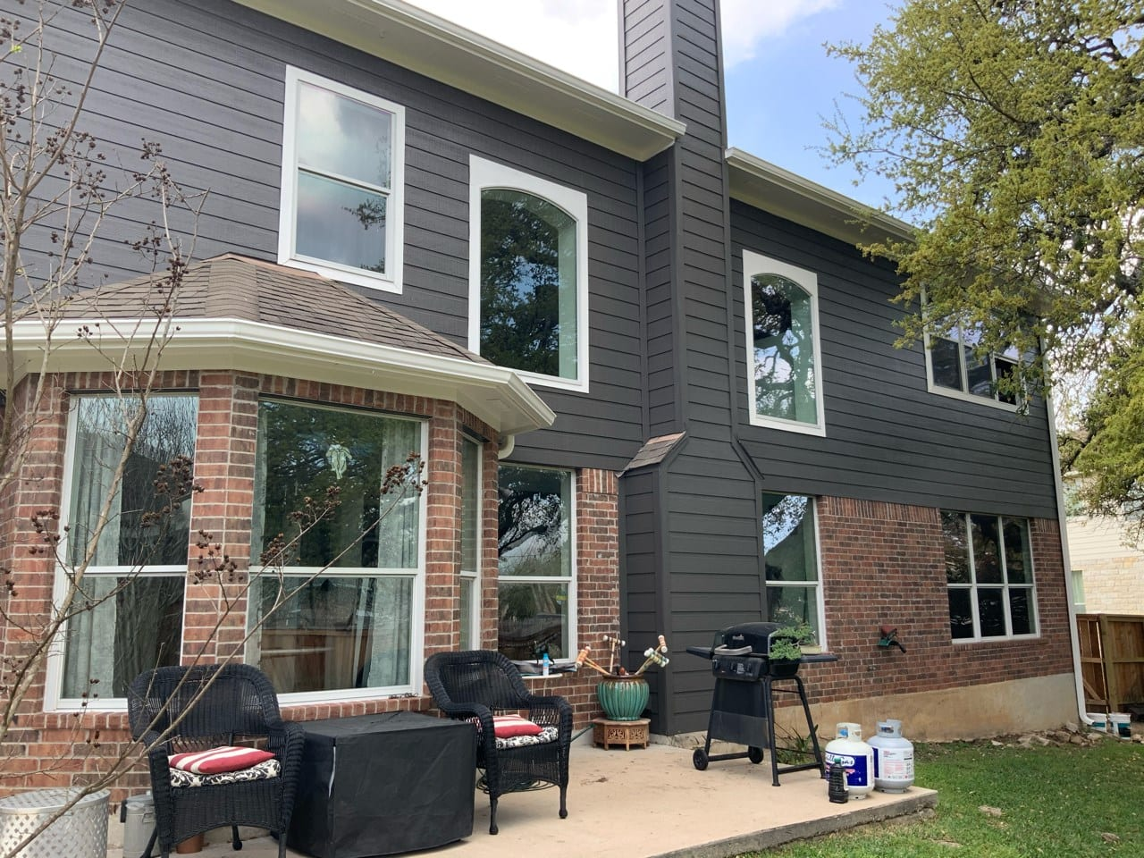 rear view red brick home with dark painted siding
