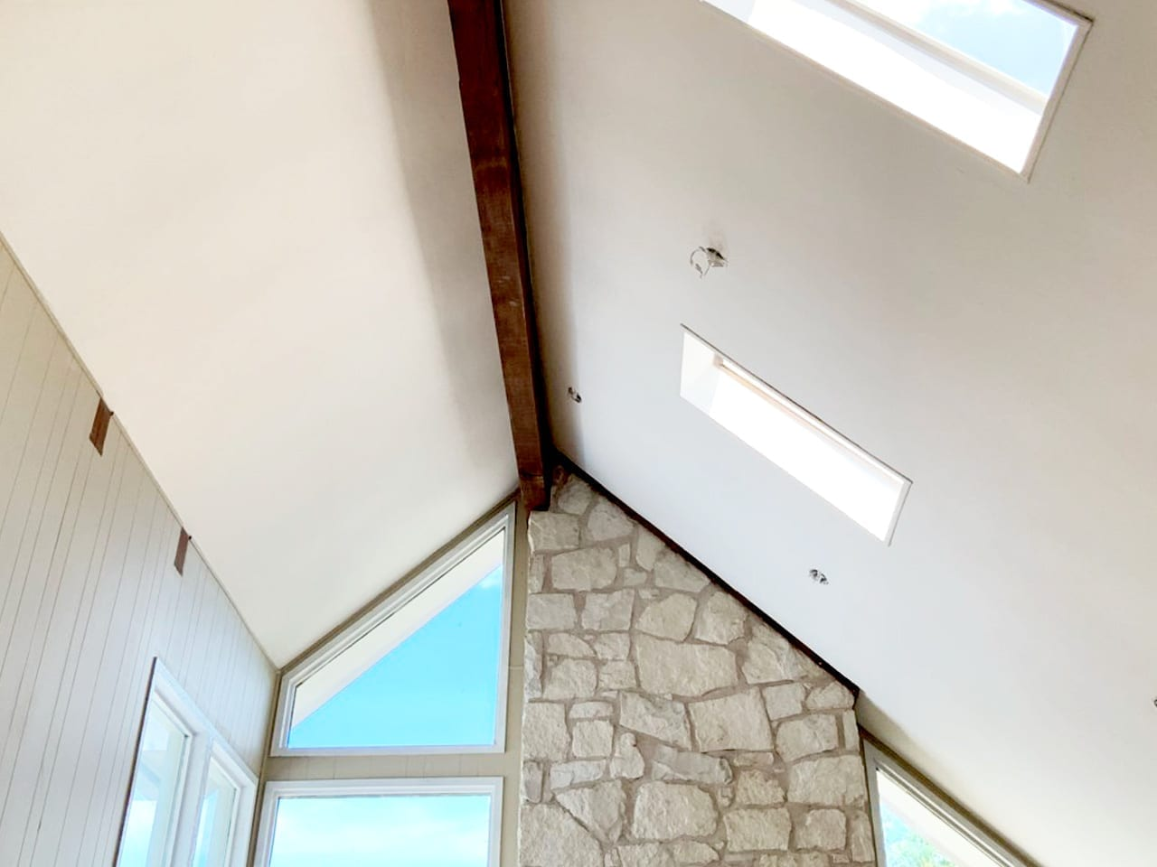 vaulted living room ceiling with beam and smooth texture