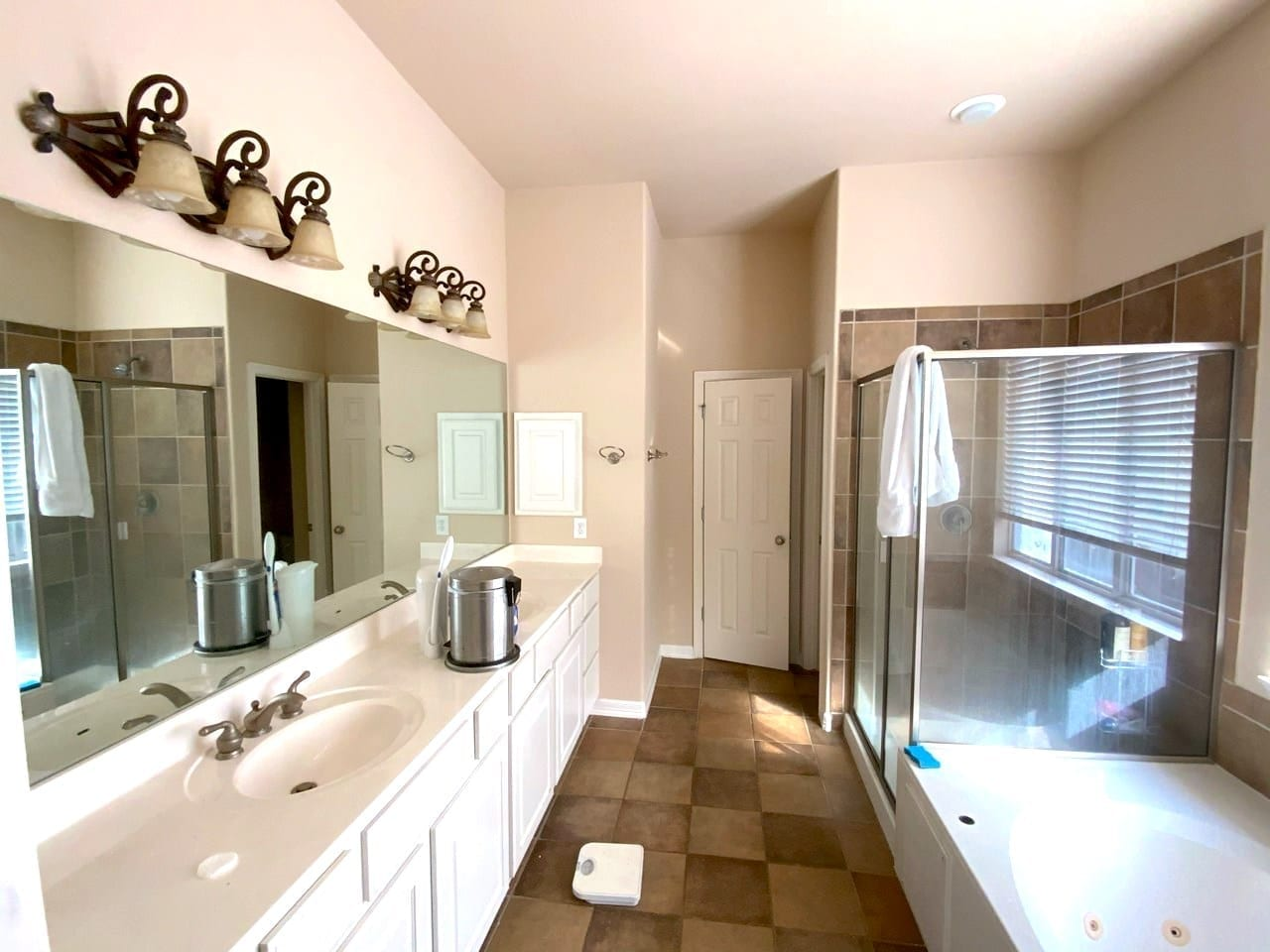 beige master bathroom with white cabinets