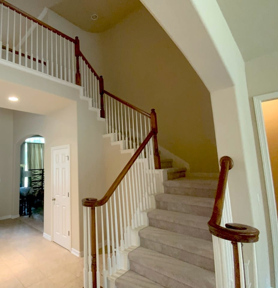 carpeted staircase with wood handrail and painted balusters