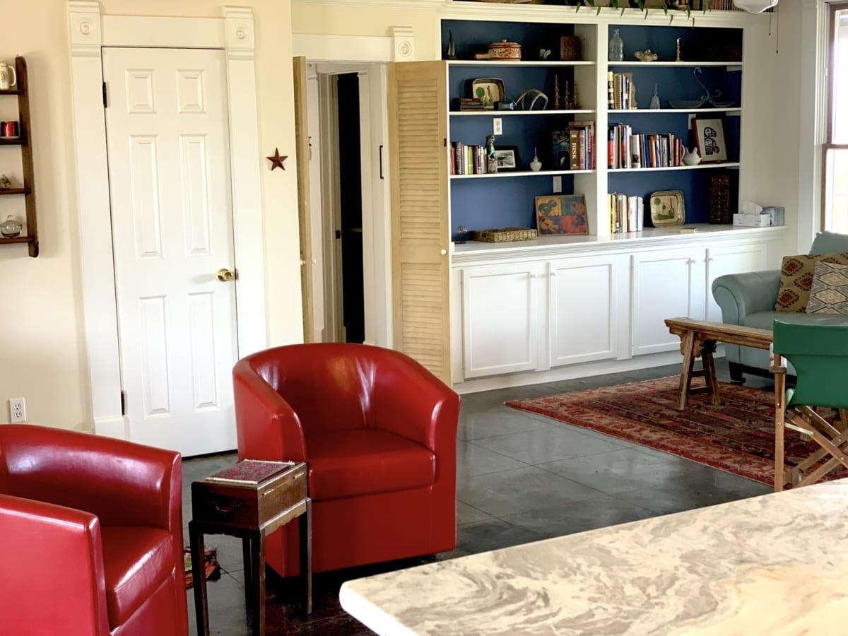 living room with red chairs and blue bookcase background