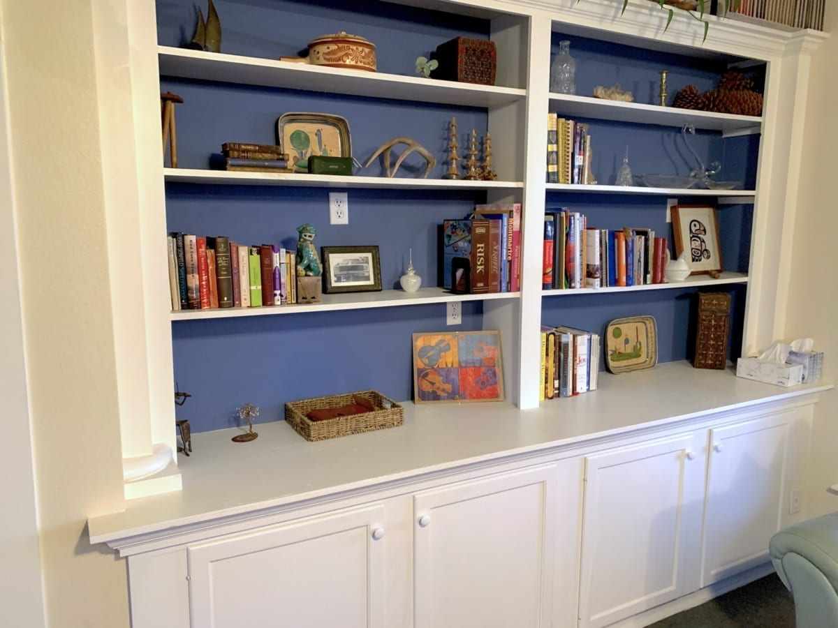 white built-in bookcase with blue contrast background