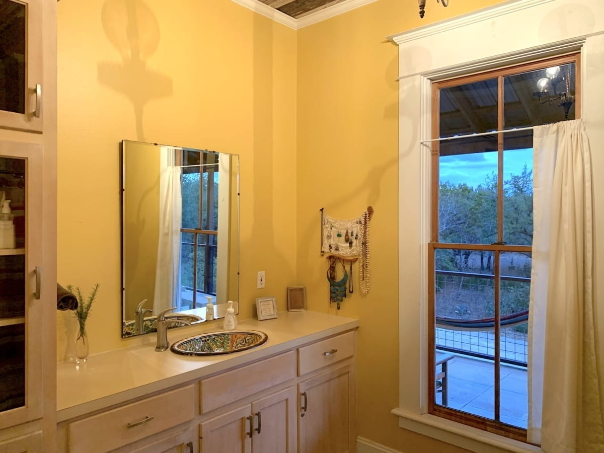 yellow bathroom with wood cabinets